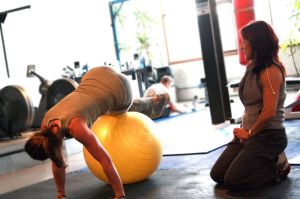 800px-Personal_trainer_monitoring_a_client's_movement_during_a_fitball_exercise